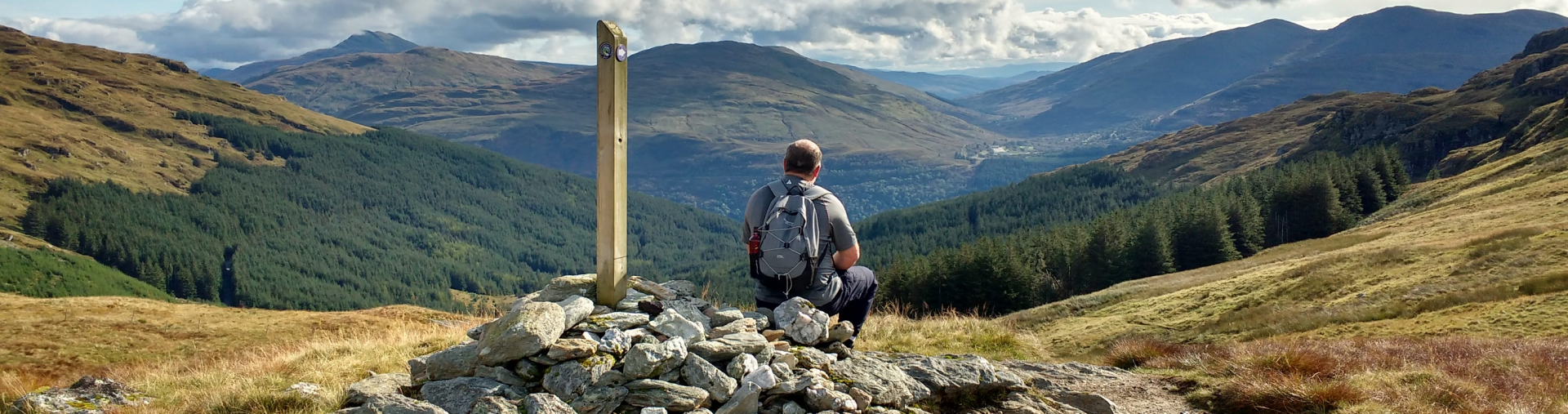 A walker sits at a waymarker overlooking a forested valley - tranquil holidays with corporate discounts