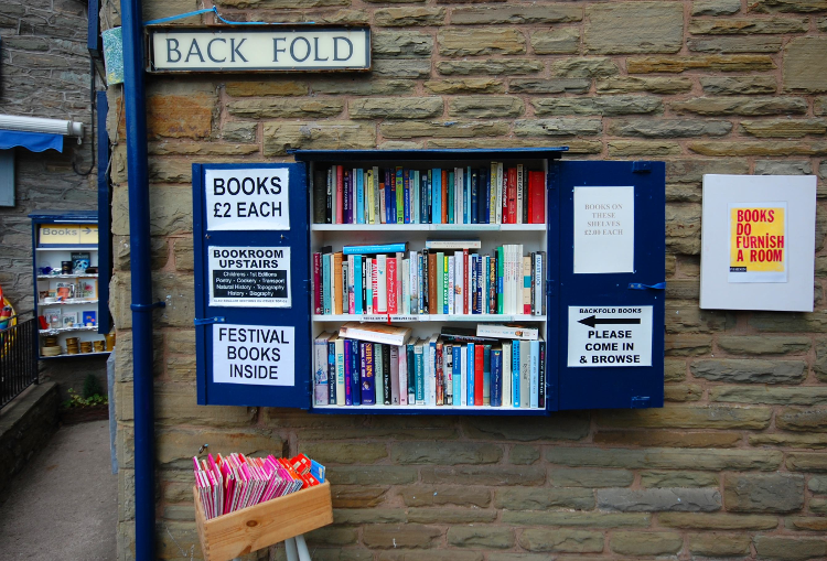Books sold from a hatch on a stone wall in Hay-on-Wye