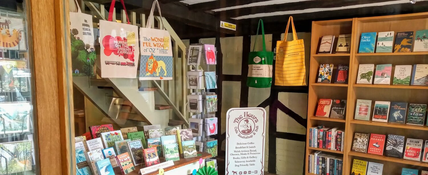 Inside the Hours Bookshop on the Usk Valley Way, with shelves of books and hanging canvas bags